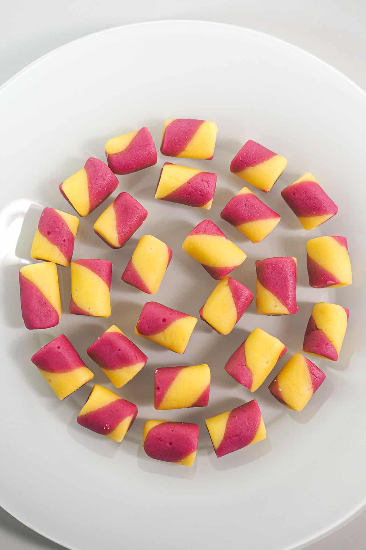 Pink and yellow butter mint candy arranged in a circular motion on a white plate