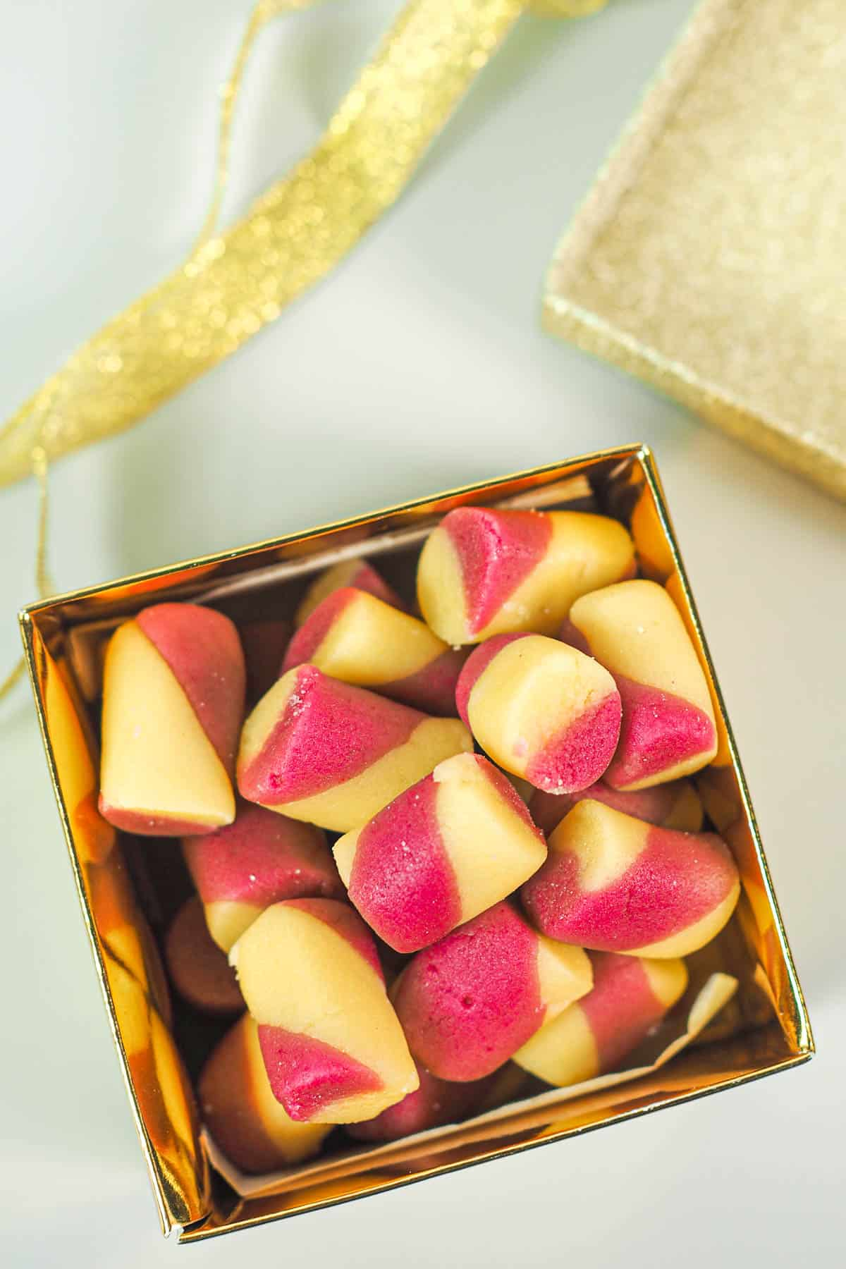 Pink and yellow homemade butter mints in a gold box