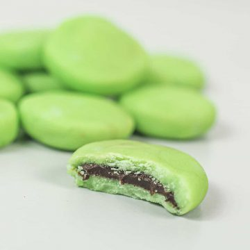 A bitten chocolate mint candy with more mints in the background