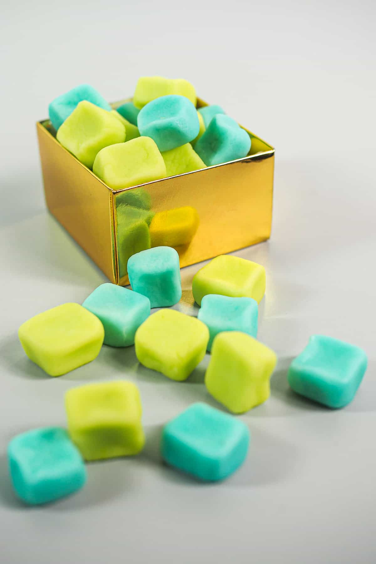 A gold box of blue and green square candies, with some candies outside the box.