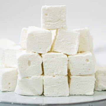 A bunch of square marshmallows stacked up on a white plate