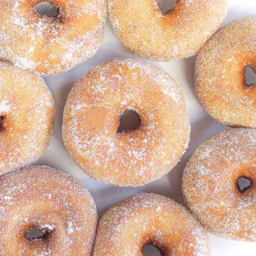 Close up of ring donuts coated in sugar on a plate