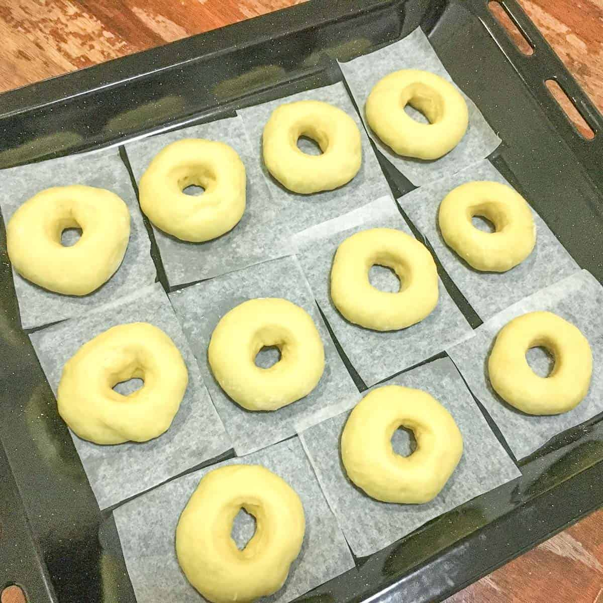 Cut ring donuts on parchment squares on a large black tray
