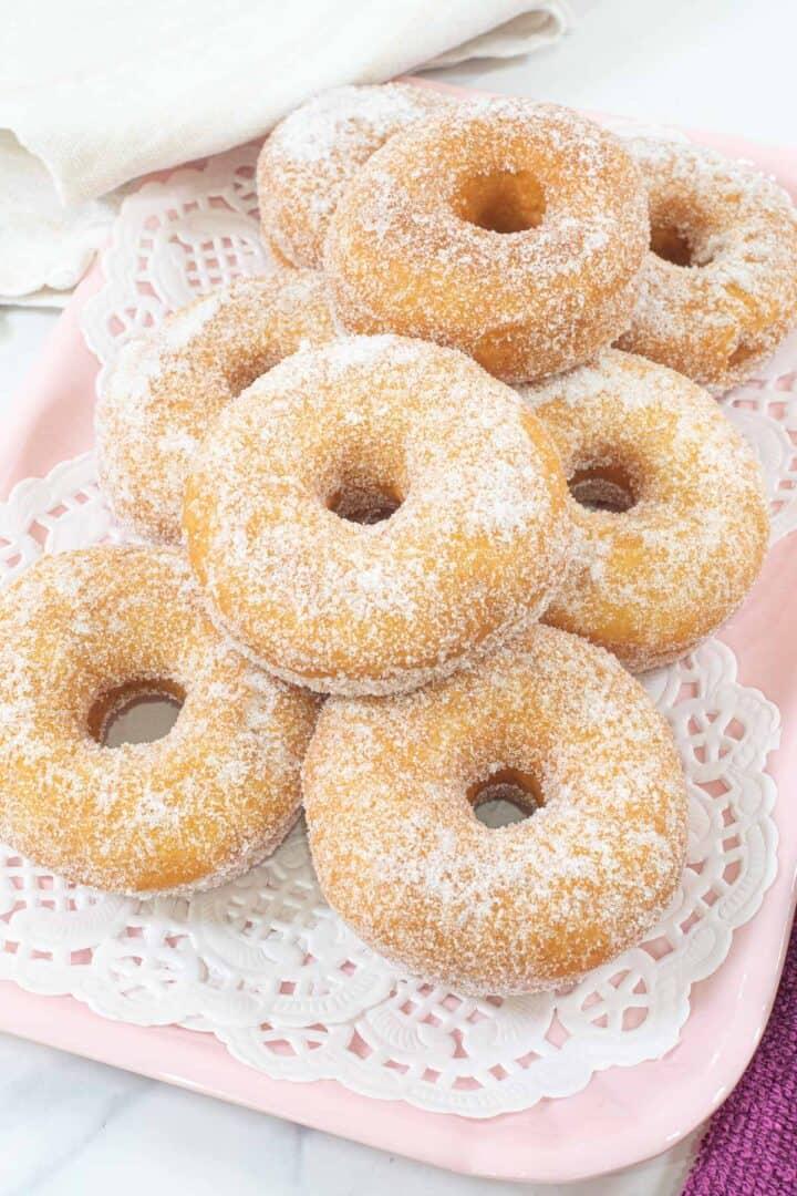 A tray of sugar coated ring doughnuts