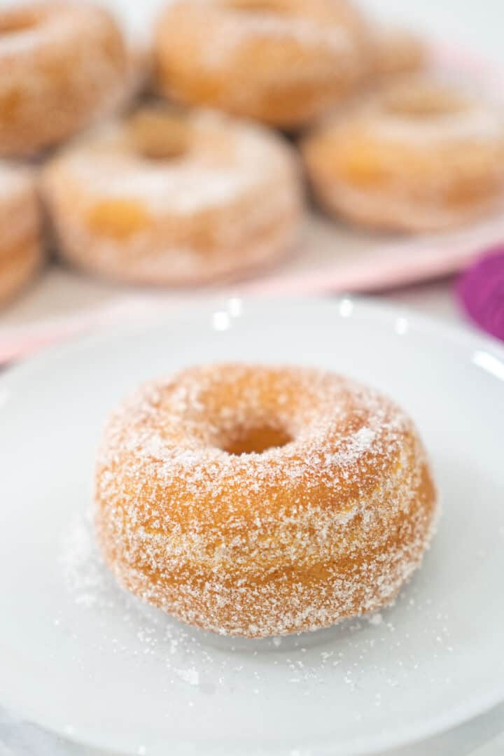 A sugar coated, ring doughnut on a white plate. In the background is a pink tray of doughnuts