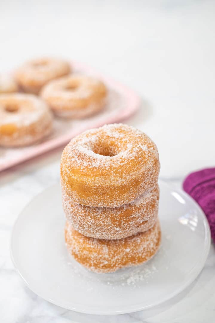 A stack of 3 doughnuts on a white plate
