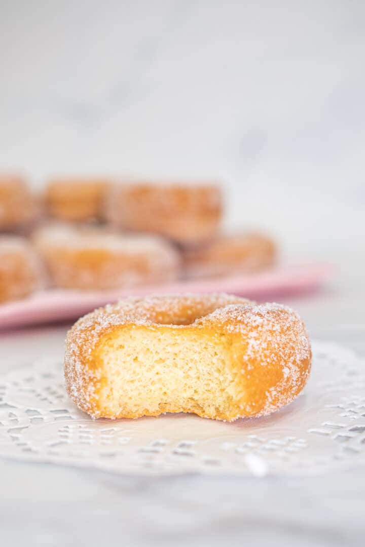 A ring doughnut with a section of it bitten out.