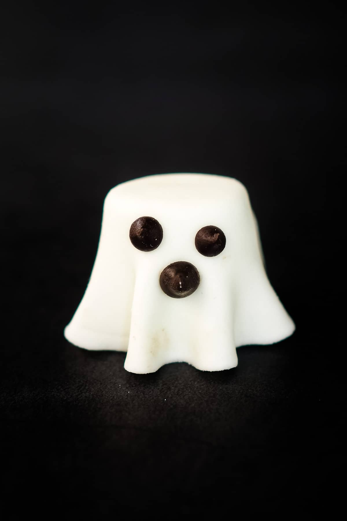 A marshmallow ghost made of fondant and marshmallow and chocolate chips