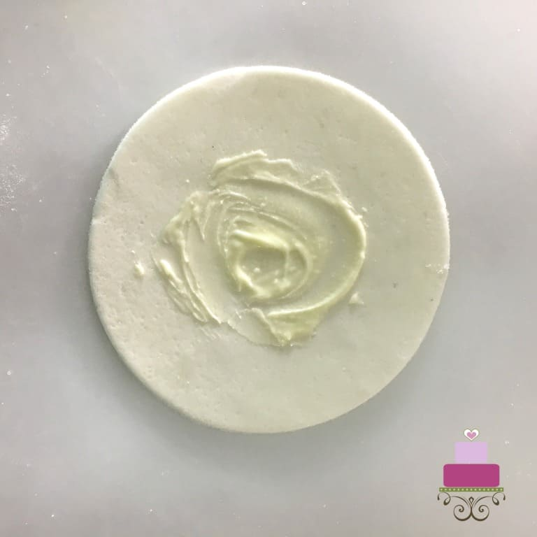 A round fondant cut out with some melted white chocolate applied in the middle
