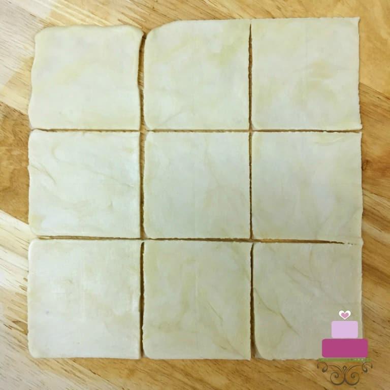 A square piece of dough cut into 9 smaller squares