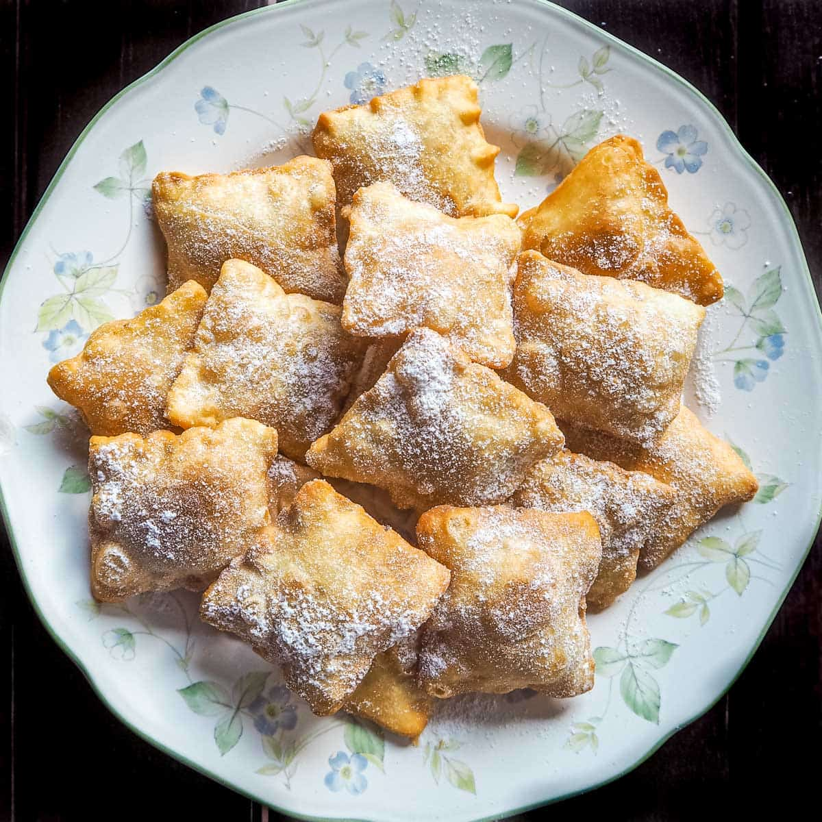 Fried square pastry puffs on a white plate