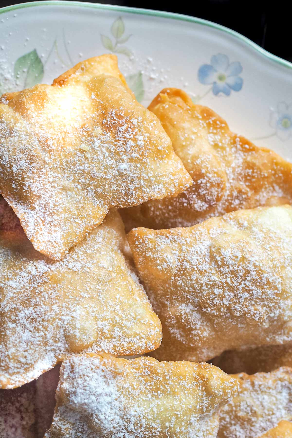 Fried pastry dough dredged with icing sugar