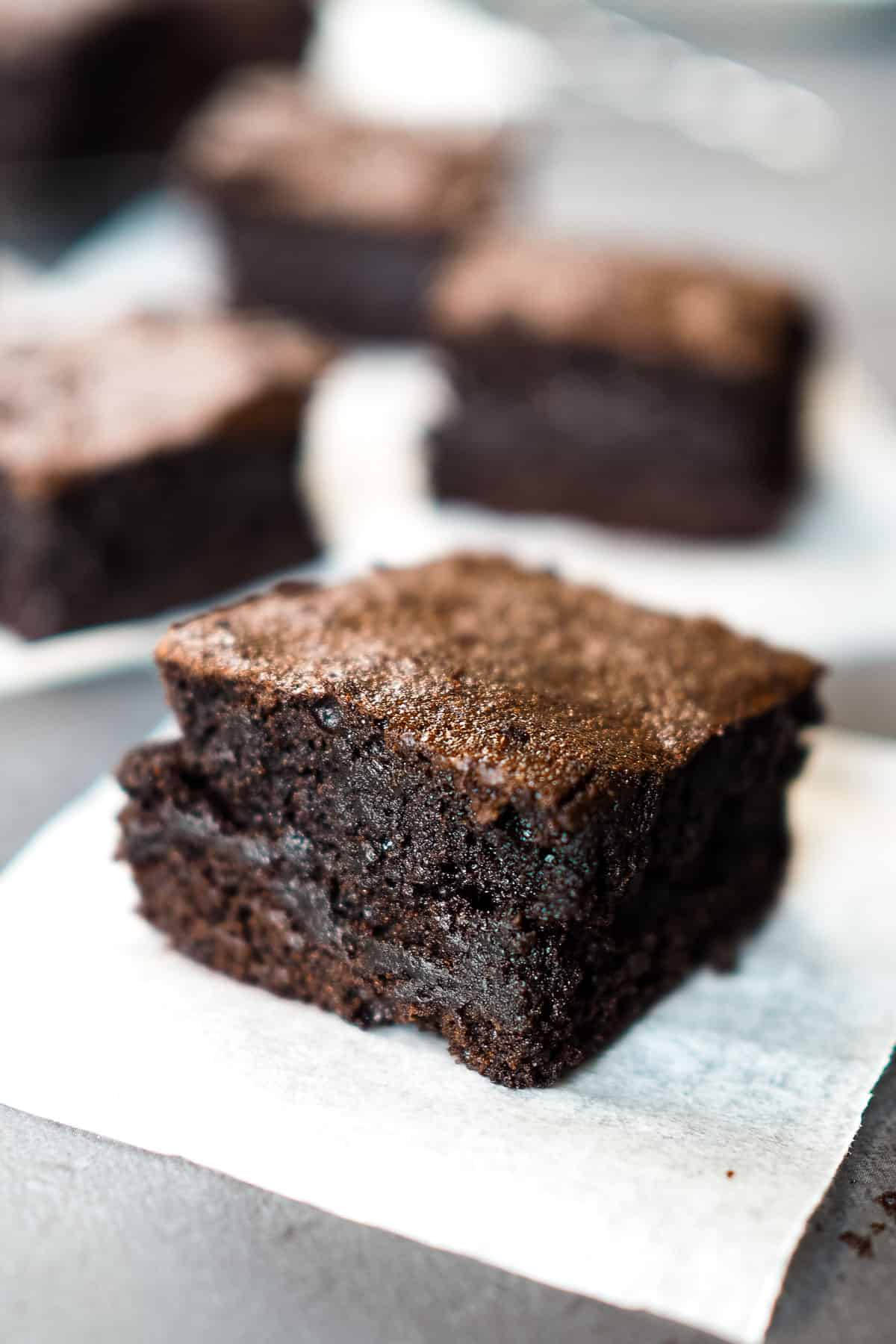 Close up of a square piece of dark and fudgy cocoa powder brownies