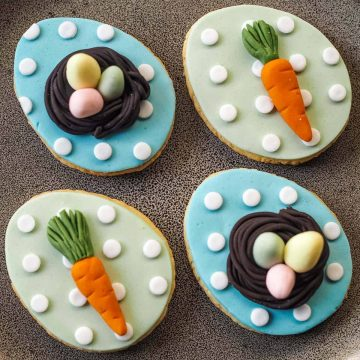 4 ggg shaped cookies in 2 design. First design with in blue background and white polka dots with 3D bird nest and 3 pastel green, pink and yellow fondant eggs in. The second design is green background with white polka dots and fondant carrot.