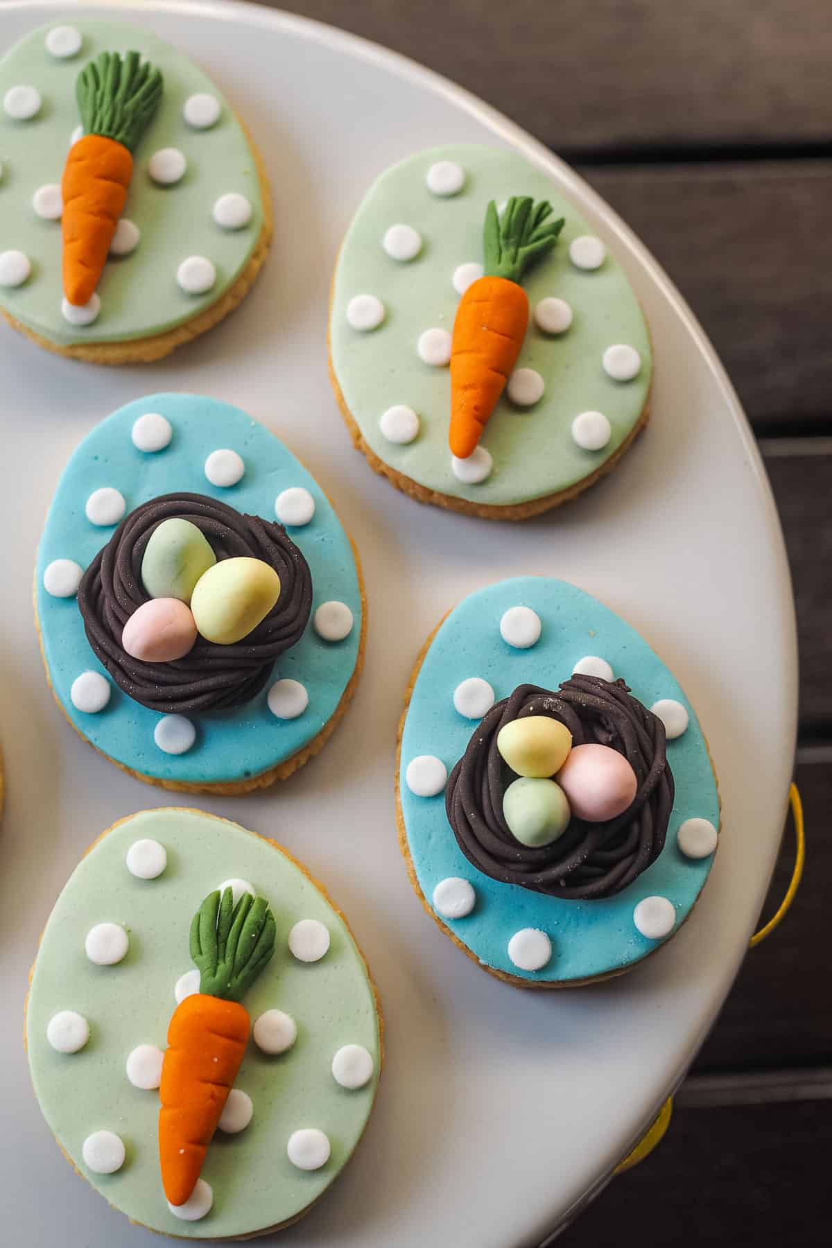Egg shaped cookies in 2 design. First design with in blue background and white polka dots with 3D bird nest and 3 pastel green, pink and yellow fondant eggs in. The second design is green background with white polka dots and fondant carrot.