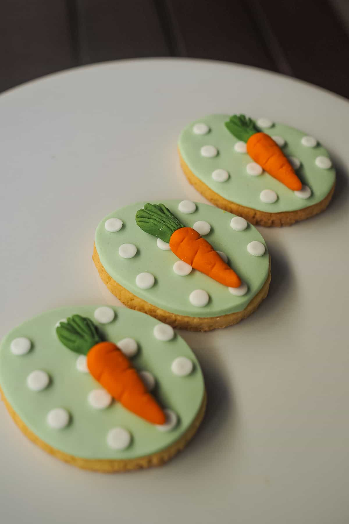 3 egg shaped Easter cookies with light green background and white polka dots. Each cookie is decorated with an orange fondant carrot