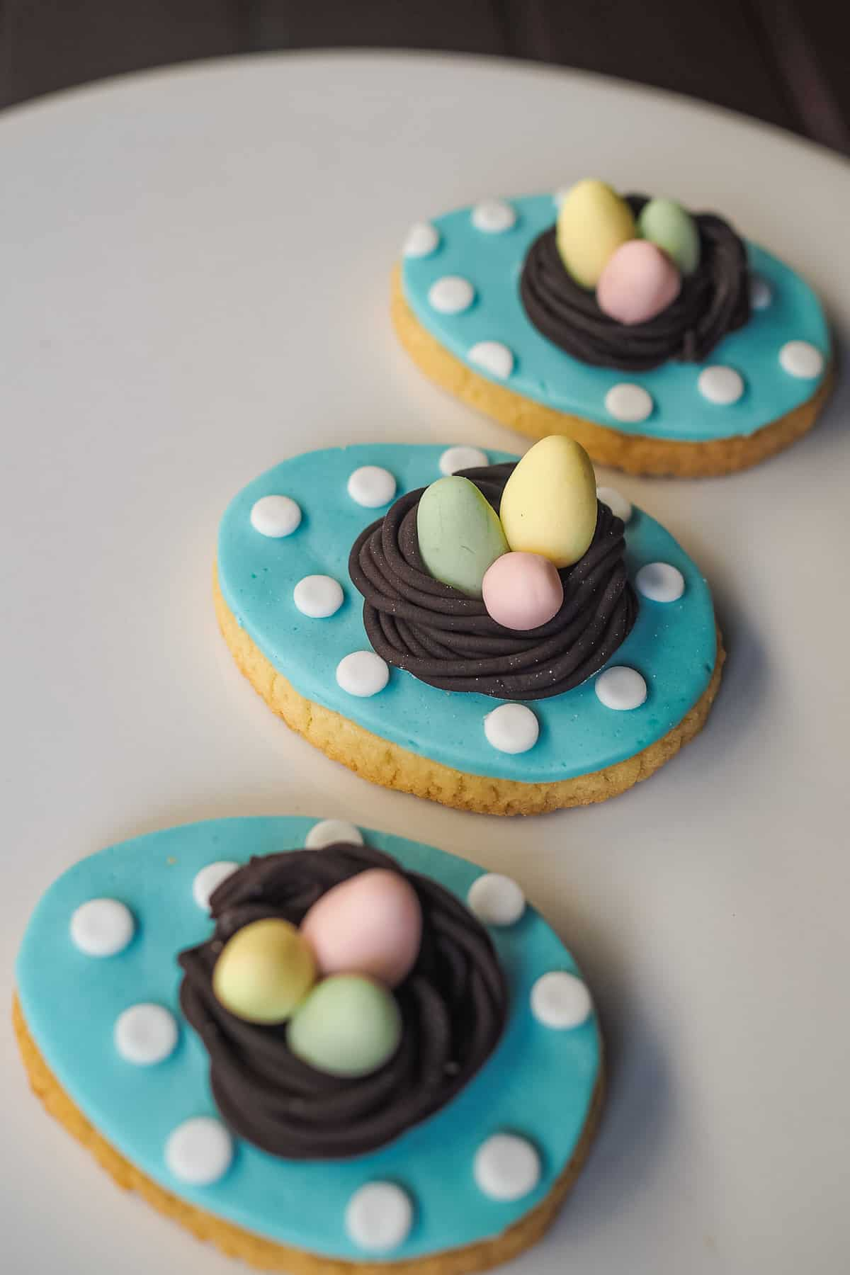 3 egg shaped cookies decorated in fondant. The background is blue with white polka dots. On each cookie is a dark brown fondant bird nest with 3 pastel fondant eggs in green, pink and yellow.