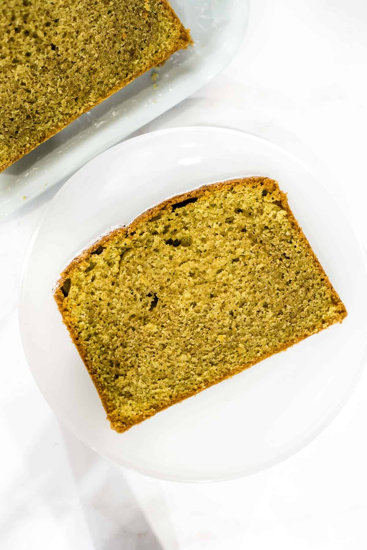 A slice of matcha pound cake on a white plate