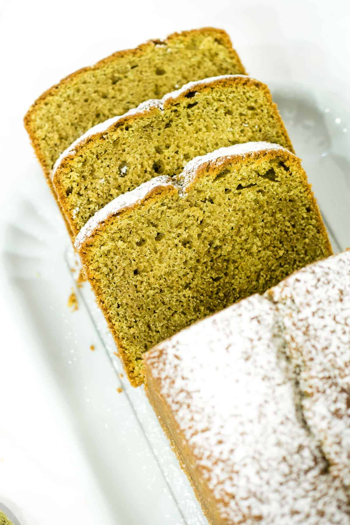 A loaf of matcha pound cake cut into slices
