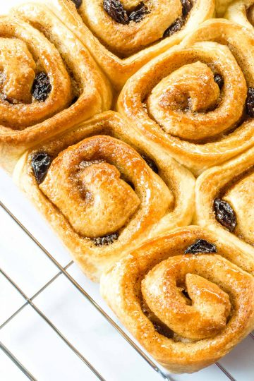 Close up of cinnamon raisin rolls on a wire rack