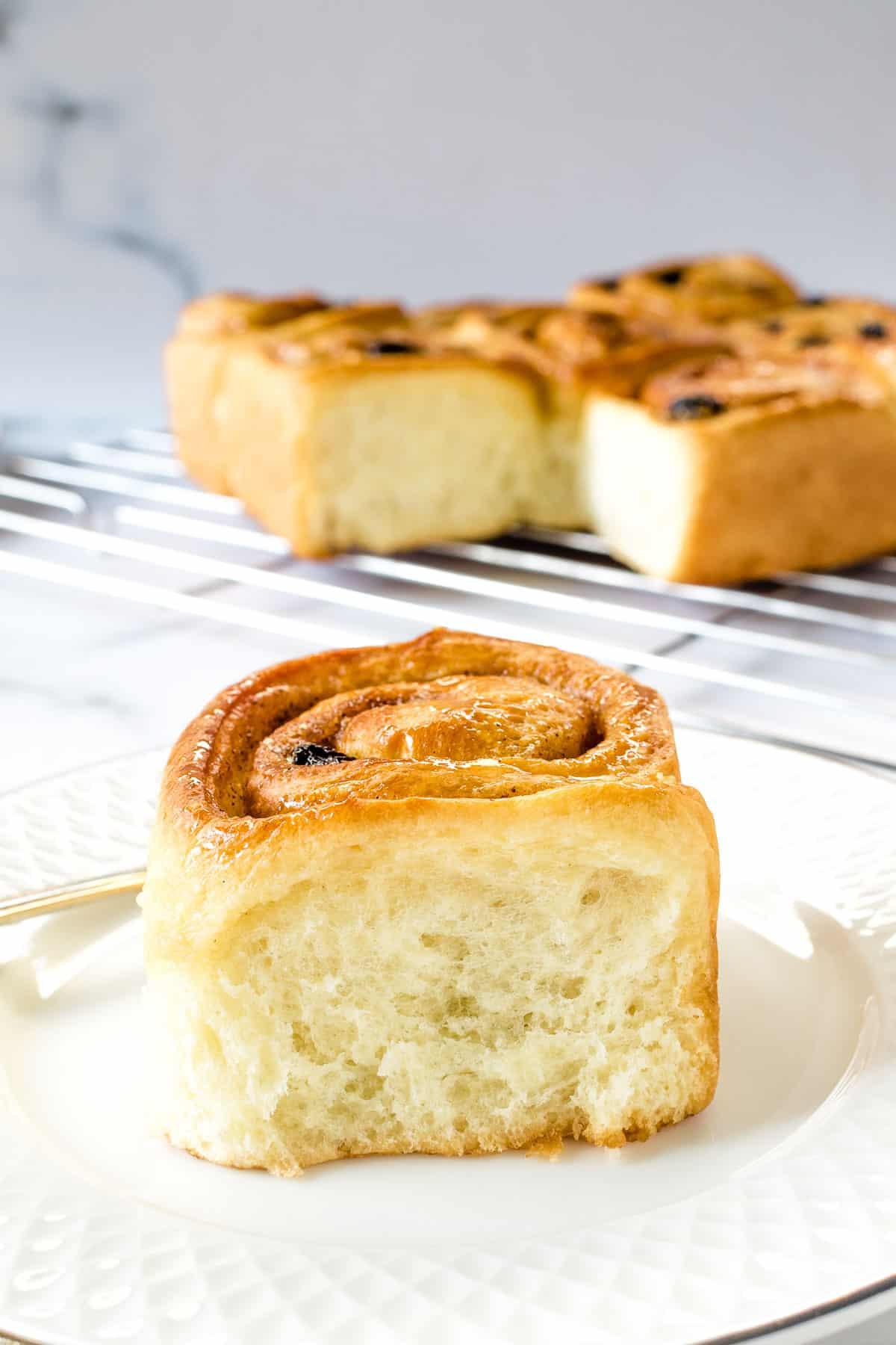 A cinnamon raisin roll on a white plate.