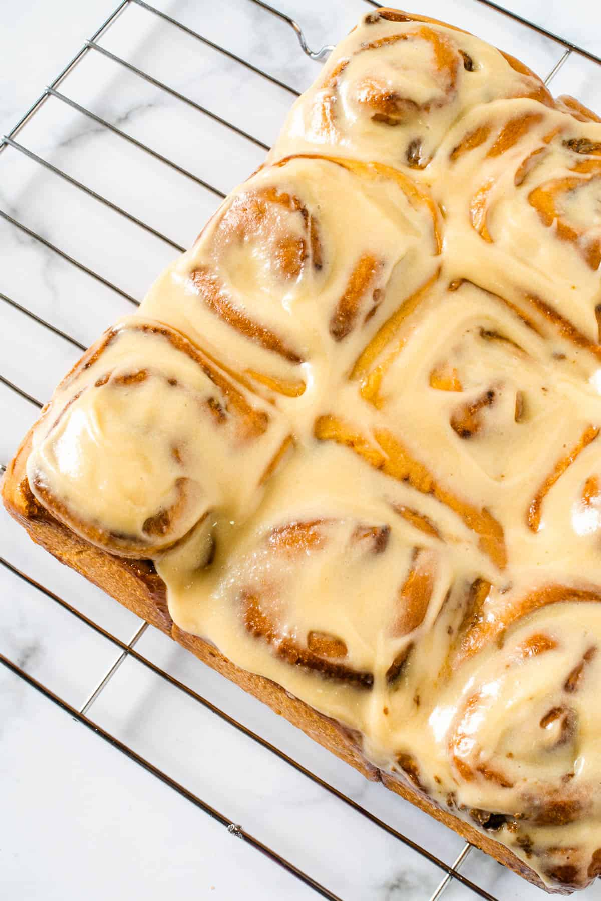 Top view of coffee rolls with coffee cream cheese glaze topping on a wire rack