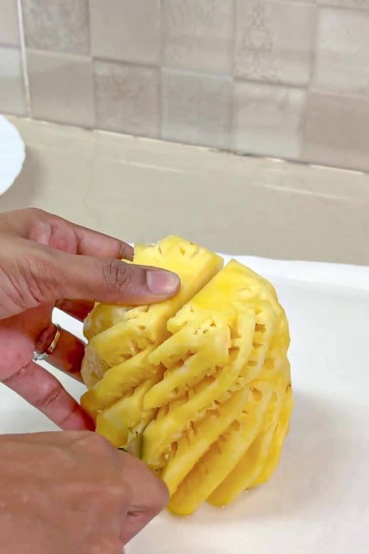 Slicing a peeled pineapple into 2