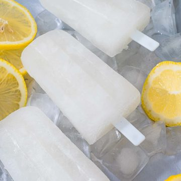 3 lemon popsicles on a tray of ice cubes and slices of lemons