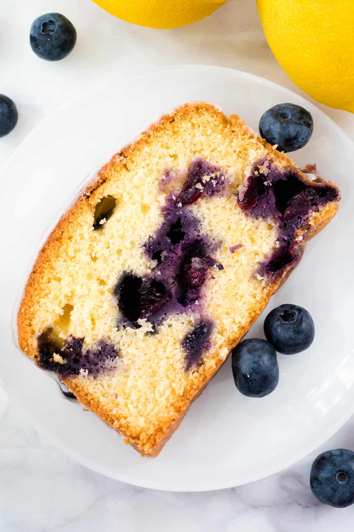 A slice of blueberry cake on a white plate