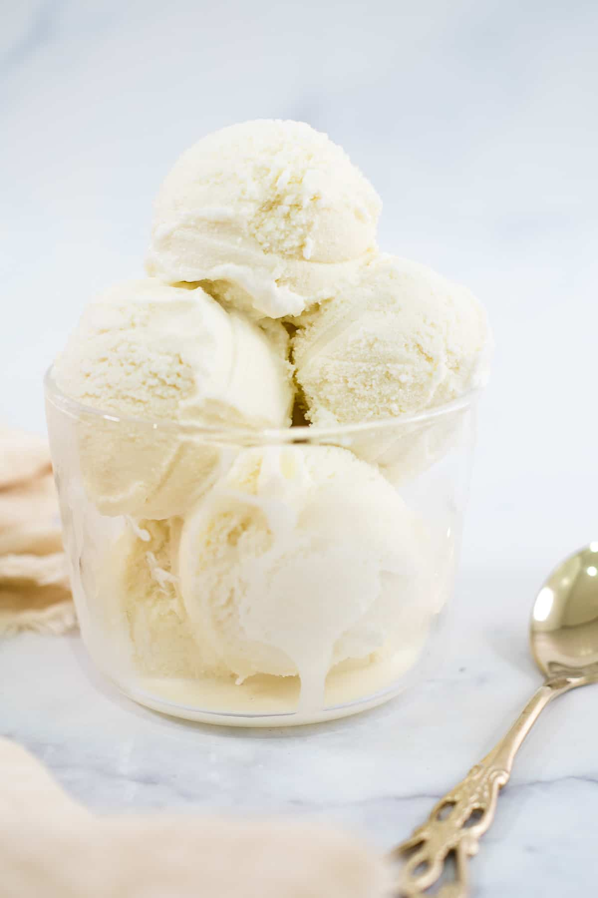 A glass bowl filled with vanilla ice cream scoops