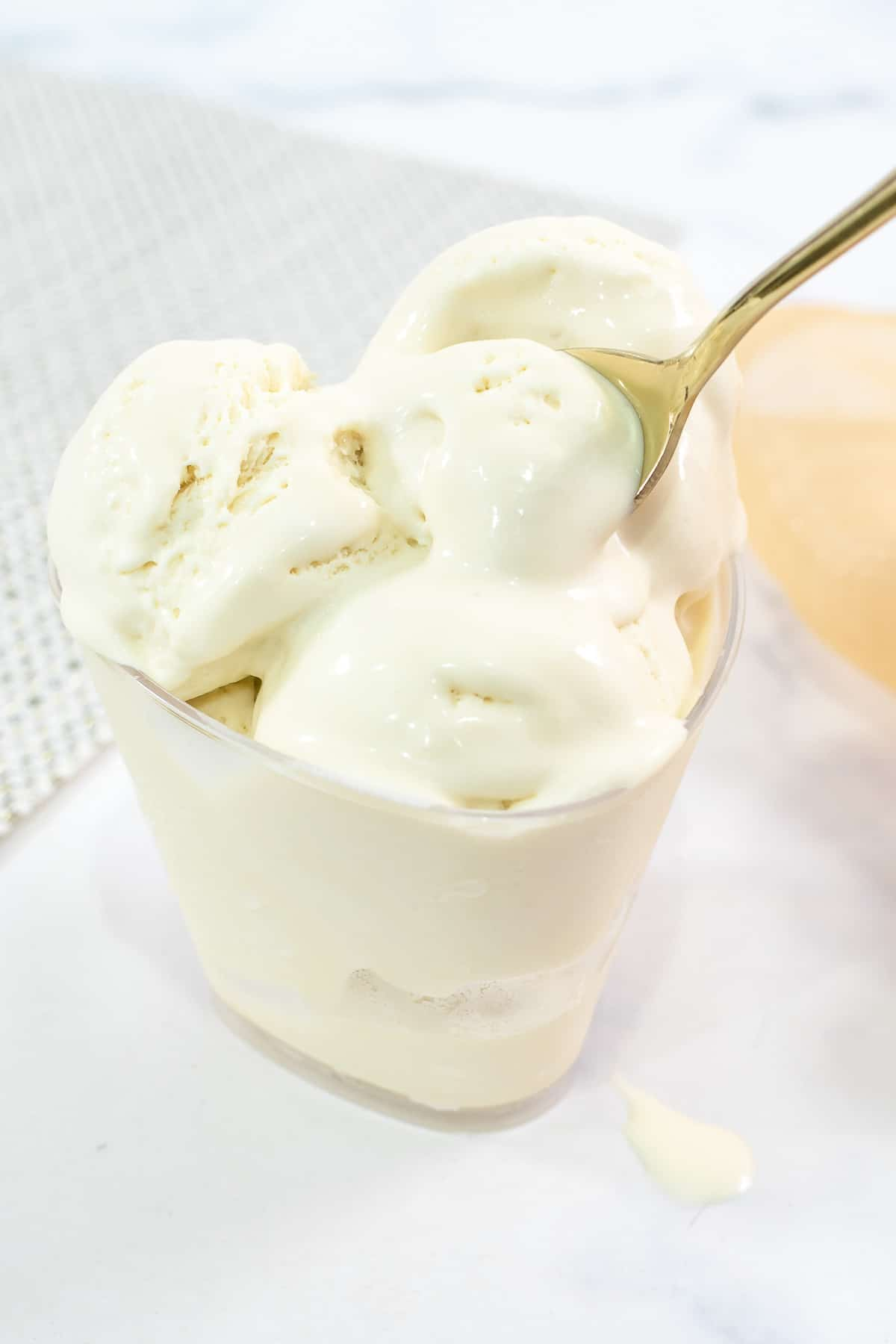 Using a gold spoon to scoop ice cream from a dessert cup