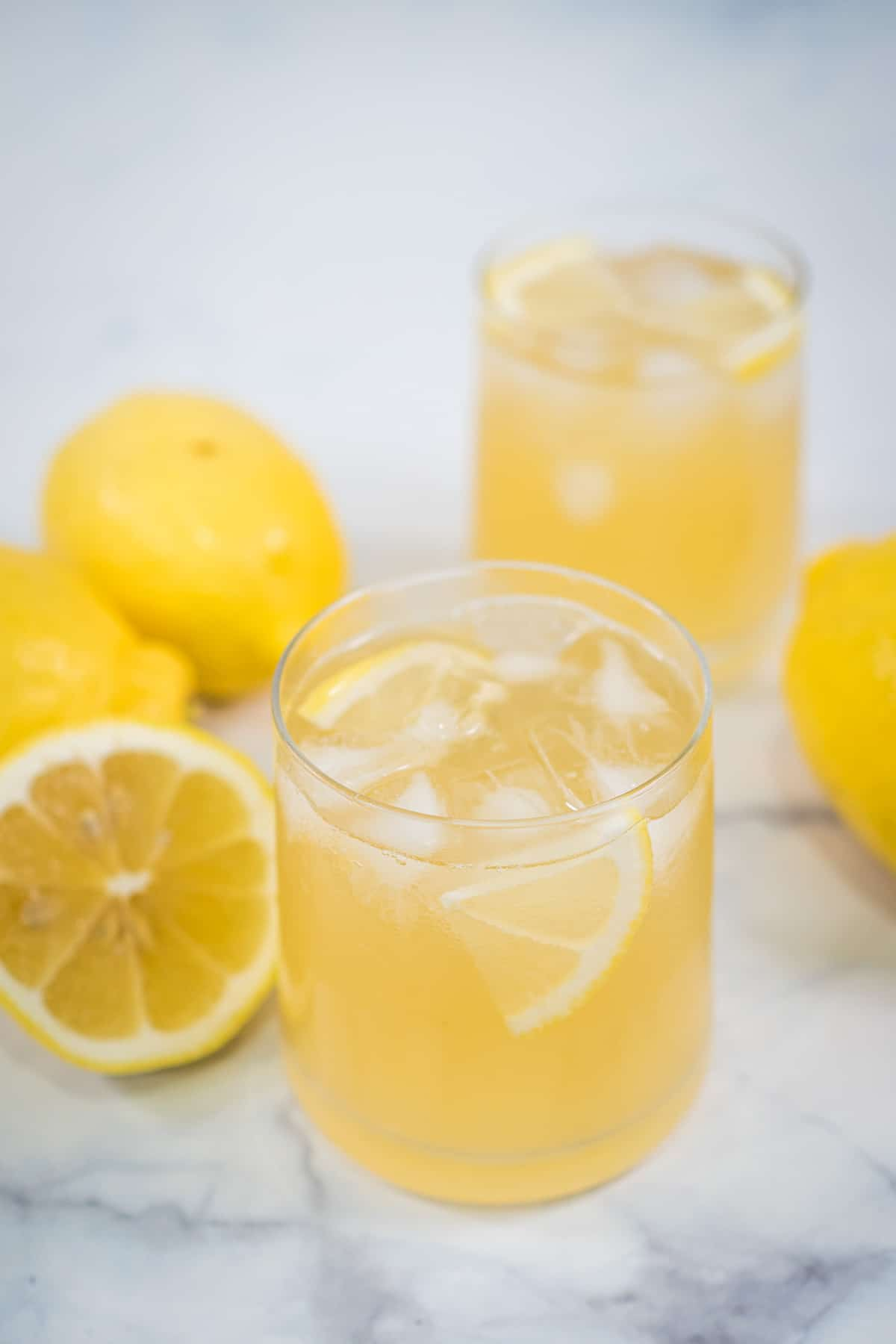 2 glasses of lemonade with ice cubes and lemon slices