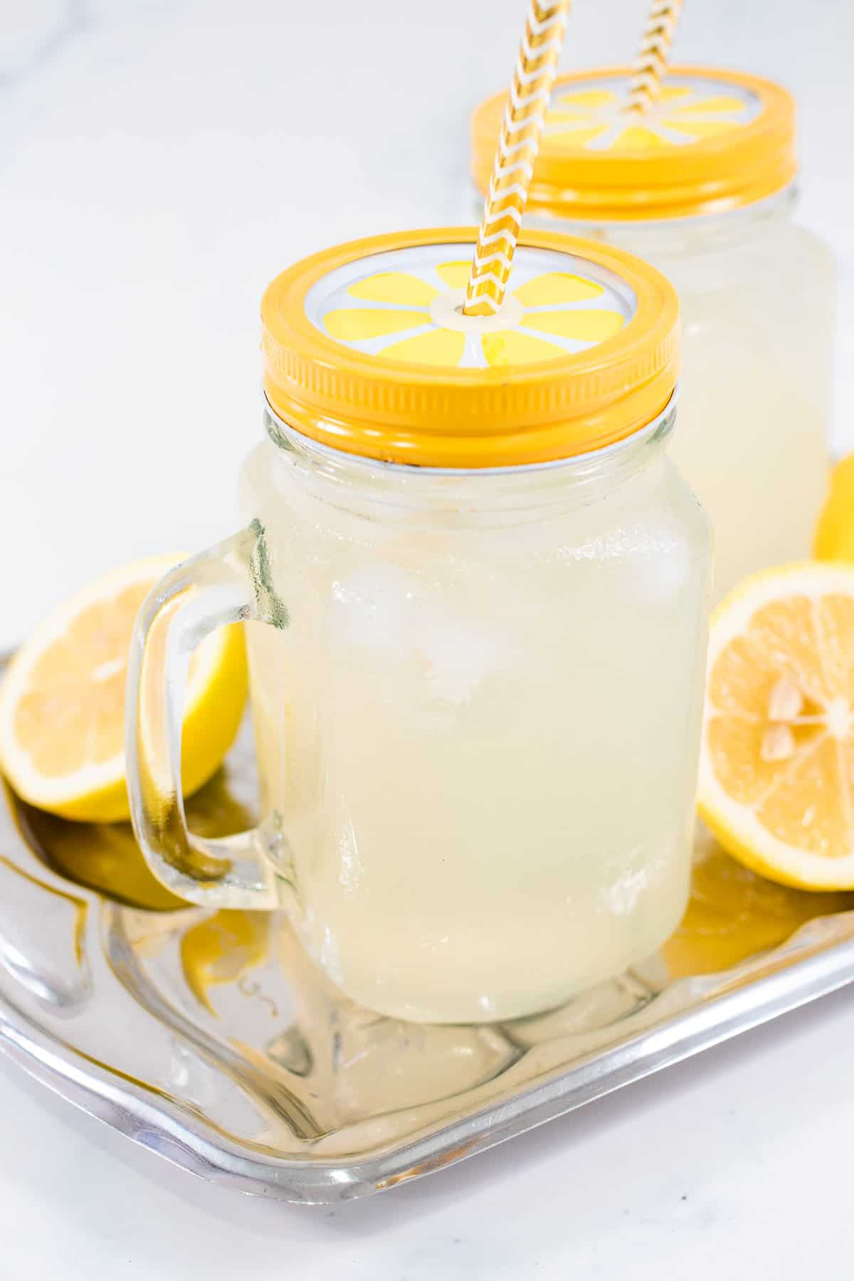 A glass of lemonade with yellow lid and straw