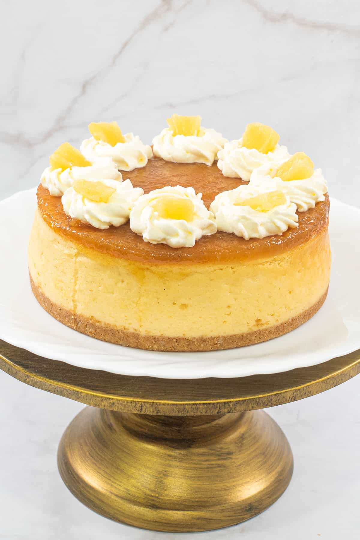A round cheesecake with pineapple filling topping on a gold cake stand