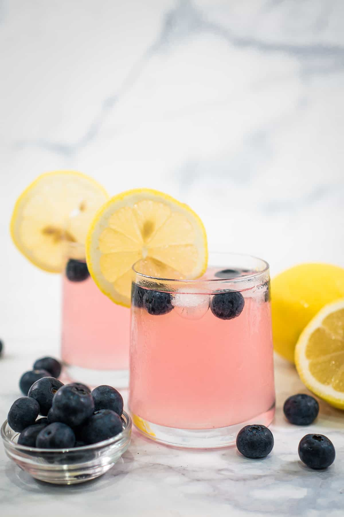 2 glasses of pink lemonade with blueberries in the glass and a slice of lemon on the rim