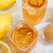 2 glasses of brown lemonade drink with caramelized lemon slices