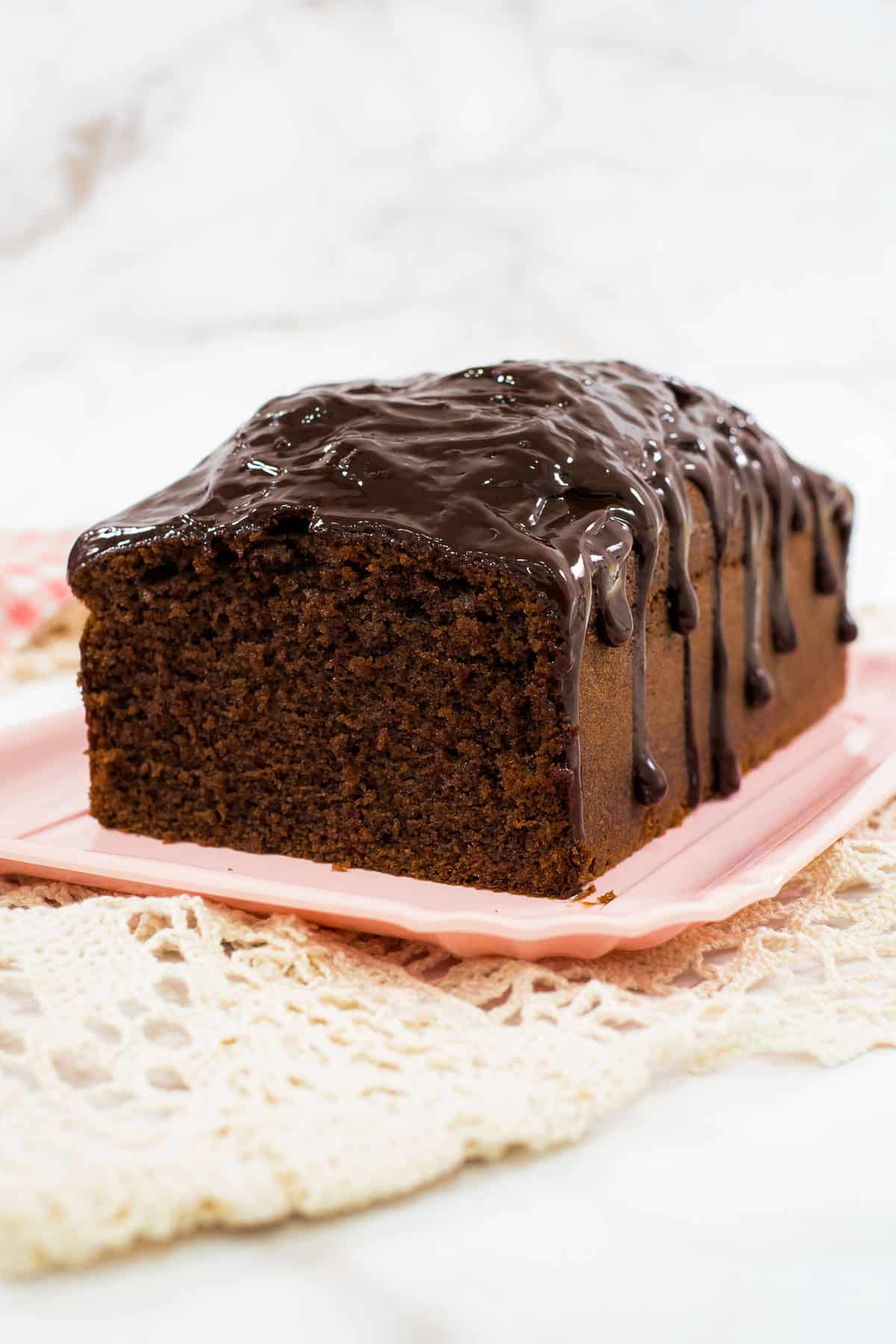 A loaf of chocolate sour cream pound cake on a pink plate
