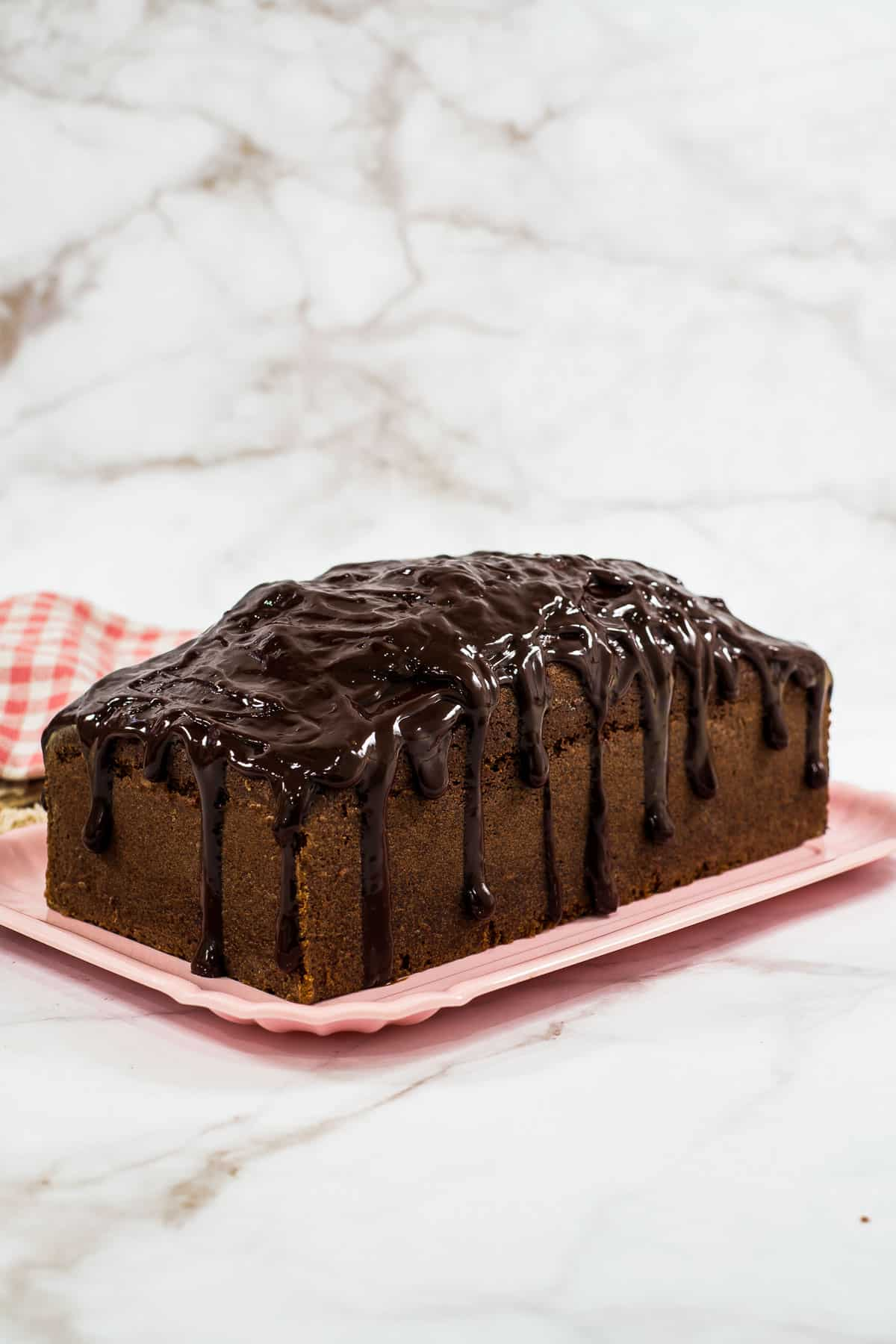 A loaf of chocolate cake with chocolate ganache topping and drips on a pink plate