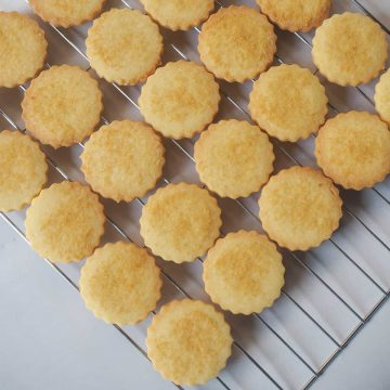 Scalloped cut out eggless sugar cookies on a wire rack