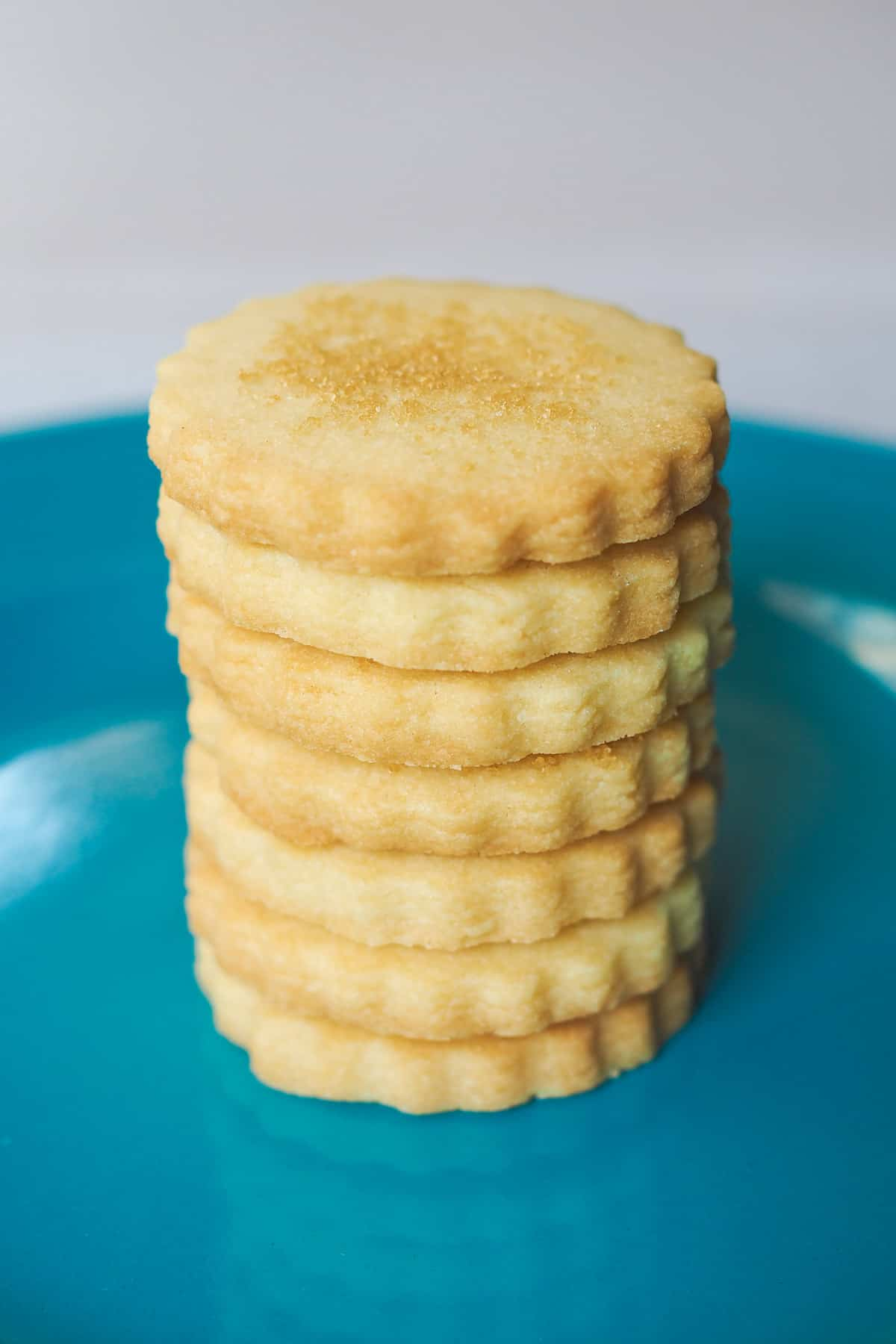 Scalloped cut out cookies staked on a blue plate
